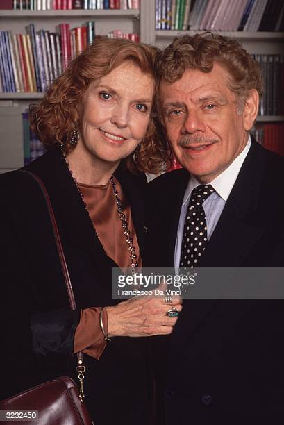 Married American comedians and actors Anne Meara and Jerry Stiller embracing in front of a bookshelf