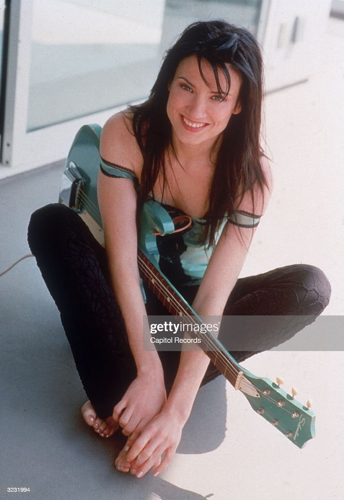 Portrait of American rock/pop singer and musician Meredith Brooks, sitting on the floor holding her turquoise guitar. She is wearing black pants and a strapless blue shirt.