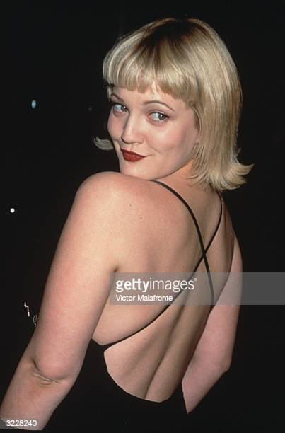American actor Drew Barrymore smiles while looking over her shoulder in a backless black dress New York City