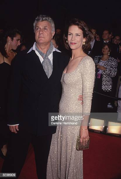 American actor Tony Curtis poses with his daughter American actor Jamie Lee Curtis on a red carpet She wears a gold dress