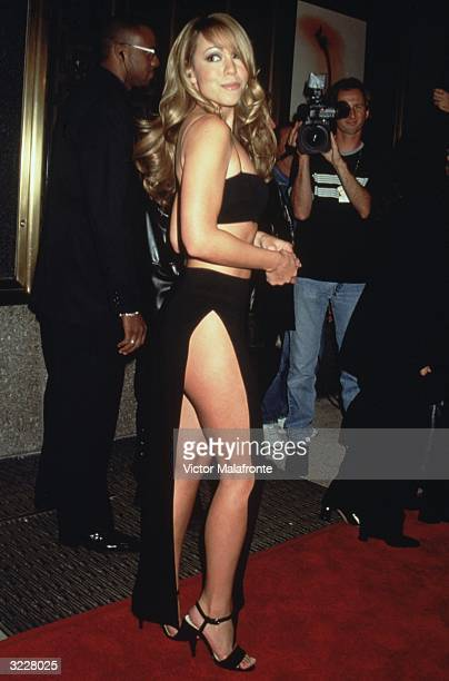 Full-length image of American singer and songwriter Mariah Carey in a halter top and long black skirt with a split up the side, New York City.