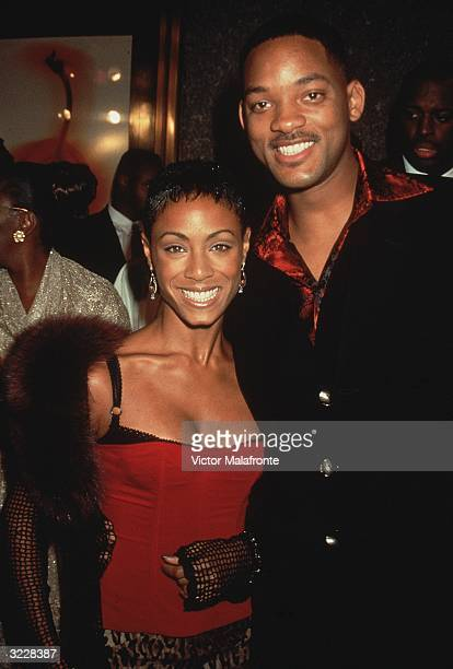 Married American actors Jada Pinkett and Will Smith posing together at an event New York City Pinkett wears a black and red bustier corset with a...