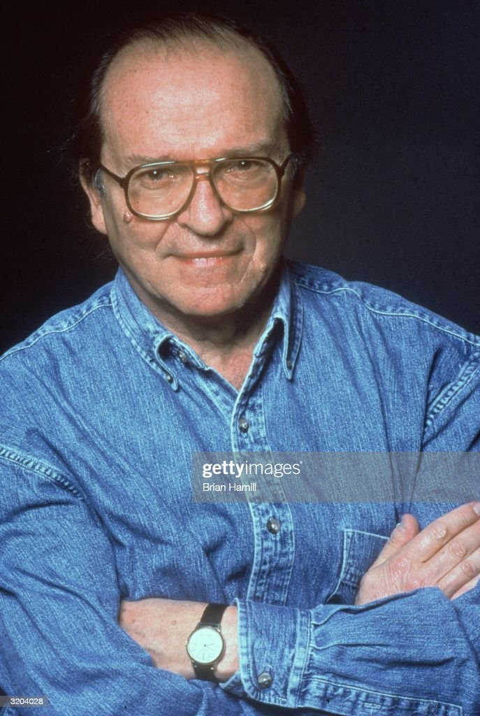 Portrait of American director Sidney Lumet, wearing a denim shirt, smiling with his arms crossed in front of his chest on the set of his film 'Gloria'. RESTRICTED, PLEASE
