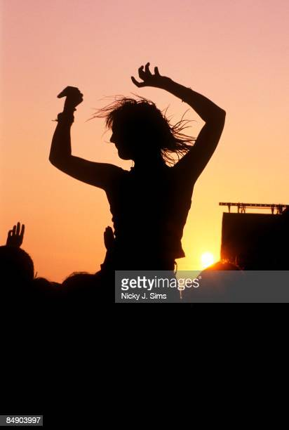 KINGDOM circa 1970 GLASTONBURY FESTIVAL Photo of CROWDS silhouette of woman sitting on shoulders above crowds at sunset at Glastonbury Festival