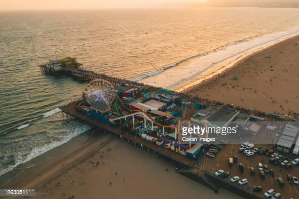 circa november 2019: santa monica pier, los angeles from above at beautiful golden hour sunset in orange light and ferrys wheel with ocean view and waves crashing - santa monica pier stock pictures, royalty-free photos & images