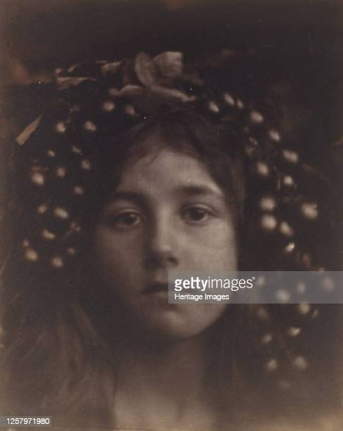 Circe 1865 A child with grapes and leaves around her head in closeup and slightly out of focus with the subject looking straight into the camera...