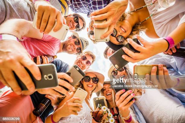 Circle of Caucasian friends posing for cell phone selfies