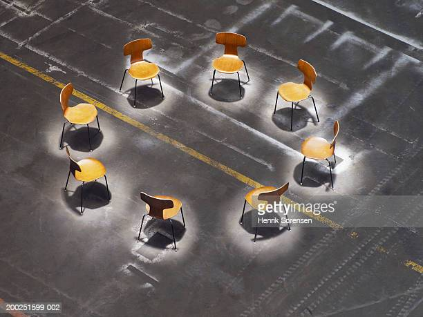 Circle of chairs under spotlights, overhead view