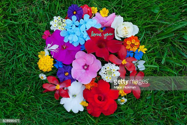 Circle of flowers on grass with words love you