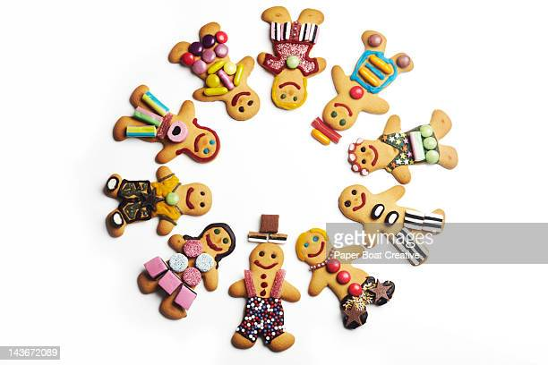 circle of gingerbread men and women with sweets - gingerbread man stock photos and pictures