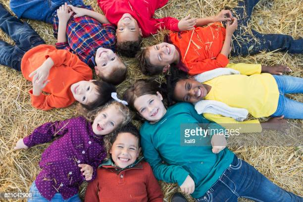 circle of multi-ethnic children lying on backs - lying down stock pictures, royalty-free photos & images