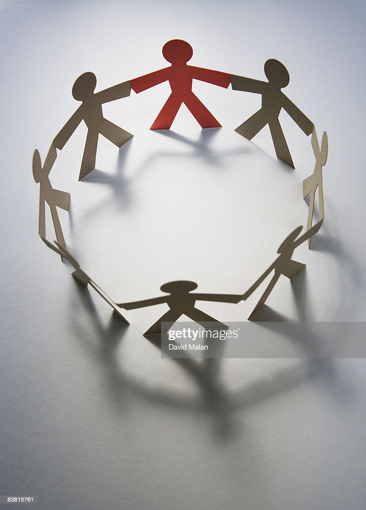 Circle of paper cut out figures, one red : Stock Photo