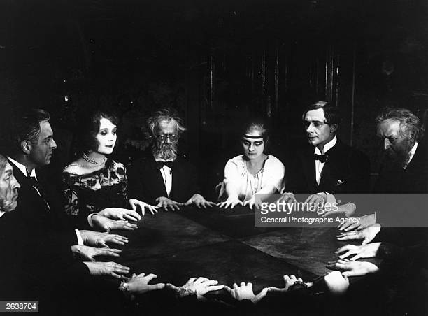 A circle of people at a spirit meeting join hands around a table and call upon the spirit World in a scene from Fritz Lang's film 'Dr Mabuse Der...