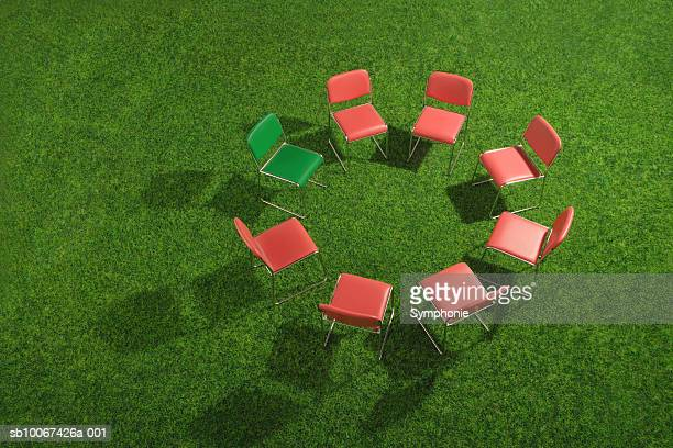 Circle of red chairs with one green on grass, elevated view