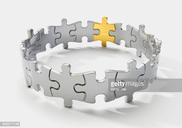 Circle of silver puzzle pieces, one gold