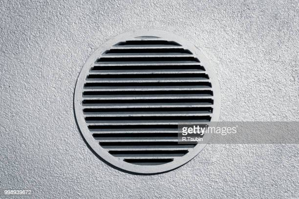 Circle vent window on metallic concrete wall