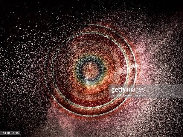 Circles of concentric colors on a black bottom of water drops