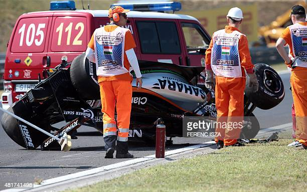 Circuit marshals clean up around the crashed car of Sahara Force India F1 Team's Mexican driver Sergio Perez during the first practice session of the...