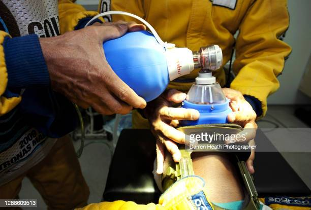 Circuit safety marshal volunteer simulates being an injured Formula one driver while being administered oxygen during FIA medical training at the...