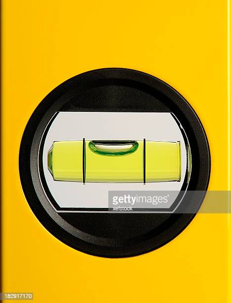 Circular bubble level on a yellow background