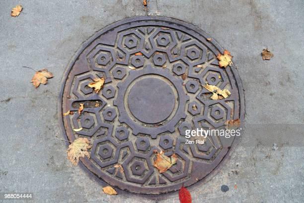 circular manhole cover on concrete pavement, quebec, canada - águas residuais imagens e fotografias de stock