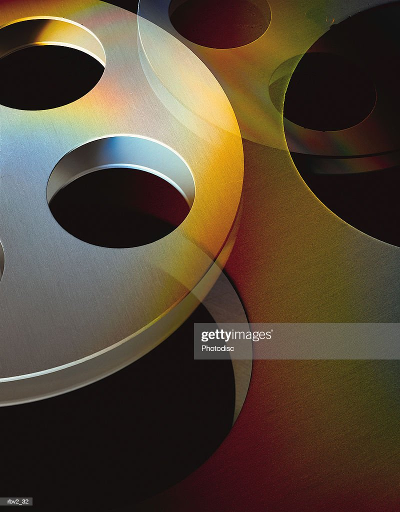 circular movie reels lie on top of each other in front of a black background : Foto de stock