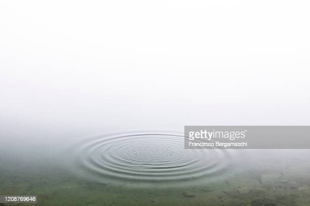 circular pattern on water surface with fog in the background. - light natural phenomenon stock pictures, royalty-free photos & images