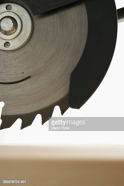 Circular saw above wooden board, close-up