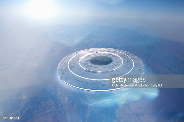 Circular UFO flying over mountain landscape