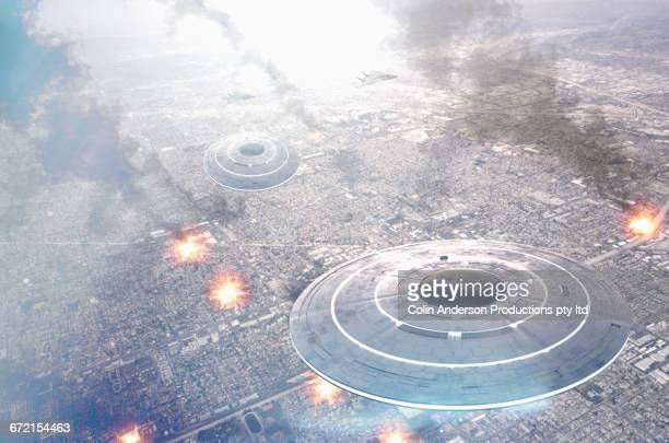 circular ufos flying over smoking city - military attack ストックフォトと画像