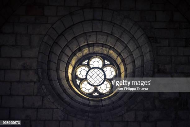 circular window in a fortified wall of st. martin church of esnandes, near la rochelle, france - katholizismus stock-fotos und bilder