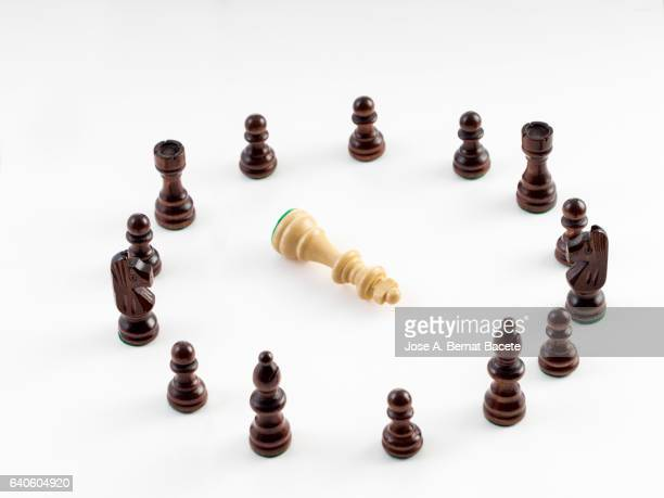 I circulate of black pieces of chess surrounding the dead king of white color