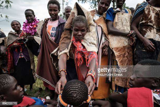 A circumcised Maasai young man receives an accessory from his mother after coming out from the bush near Kilgoris Kenya on the last day of the annual...