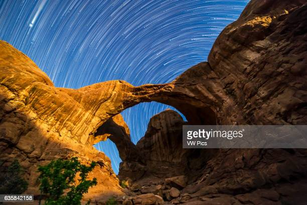 Circumpolar star trails spinning behind Double Arch at Arches National Park Utah as the waning gibbous Moon lights the arches toward the end of the...