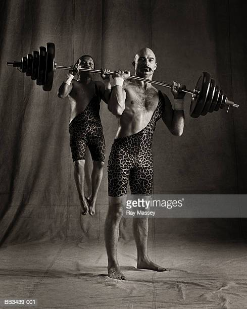 Circus dwarf hanging from barbell lifted by strongman (tinted B&W)