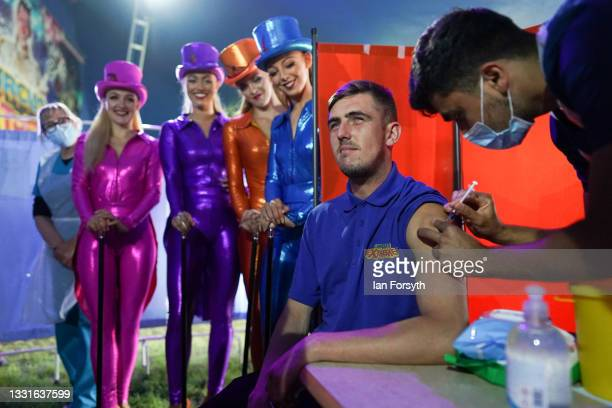 Circus lighting technician Ryan Dobie receives a Covid 19 vaccination as circus performers look on during a staged photo at a new 'Pop Up'...