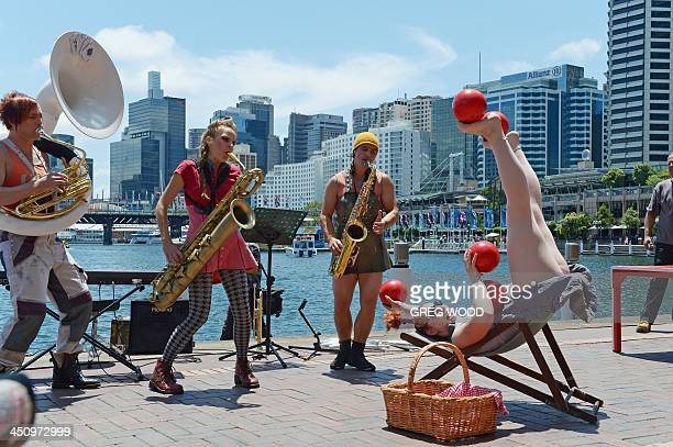 Circus Oz members Jez Davies Ania Reynolds Mason West and Hazel Bock perform at Sydney's Darling Harbour tourist precinct on November 21 2013 during...