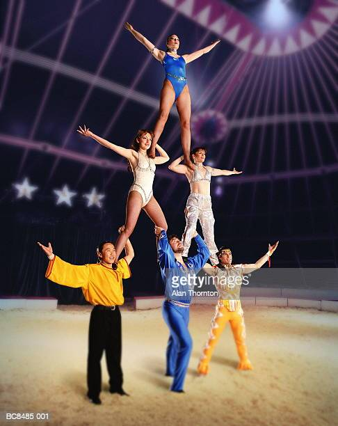 Circus performers forming human pyramid in big top (Composite)