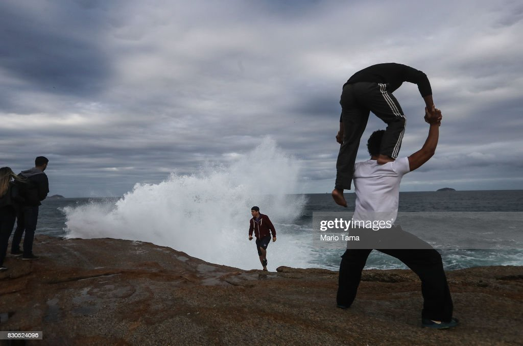 Circus performers (R) practice a pose on Arpoador rock during strong winter swells on the Atlantic Ocean on August 11, 2017 in Rio de Janeiro, Brazil. Waves were measured as high as thirteen feet in Rio today in the middle of Brazil's winter season. According to the Urban Climate Change Research Network (UCCRN), Rio's average temperature would rise around one degree Celsius between 2015 and 2020 along with a sea level rise of 14 cm. Changes in Rio's climate are projected to be the most dire of all cities in South America, according to UCCRN.
