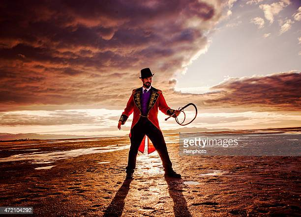 circus ring master in a dramatic desert setting - circus stock pictures, royalty-free photos & images