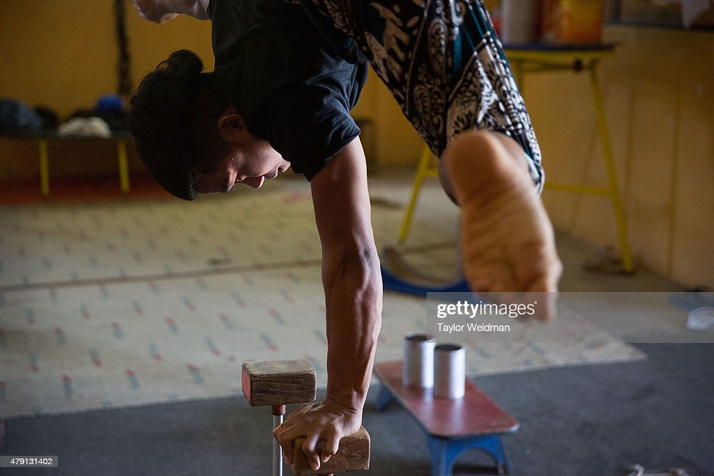 A circus student balances on one arm while practicing on July 1, 2015 at Phare Ponleu Salpak in Battambang, Cambodia. Phare Ponleu Salpak is an organization providing free education and artistic training to Cambodian children. Students in the organization's circus program often go on to careers performing both internationally and domestically at venues like Phare - The Cambodian Circus in Siem Reap.
