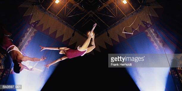 Circus trapeze act, woman in mid-leap,low angle view (Composite)
