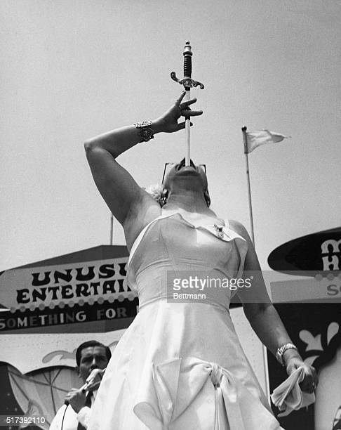 A circus woman performs a sword swallowing trick Undated photograph