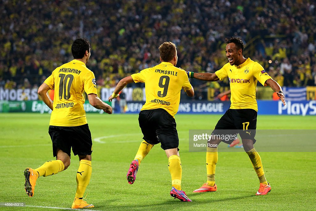 Ciro Immobile #9 of Borussia Dortmund is congratulated by teammates Henrikh Mkhitaryan #10 and Pierre-Emerick Aubameyang #17 of Borussia Dortmund after scoring the opening goal on the stroke of half time during the UEFA Champions League Group D match between Borussia Dortmund and Arsenal at Signal Iduna Park on September 16, 2014 in Dortmund, Germany.