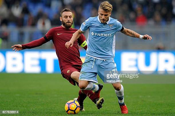 Ciro Immobile of SS Lazio compete for the ball with Daniele De Rossi of AS Roma during the Serie A match between SS Lazio and AS Roma at Stadio...