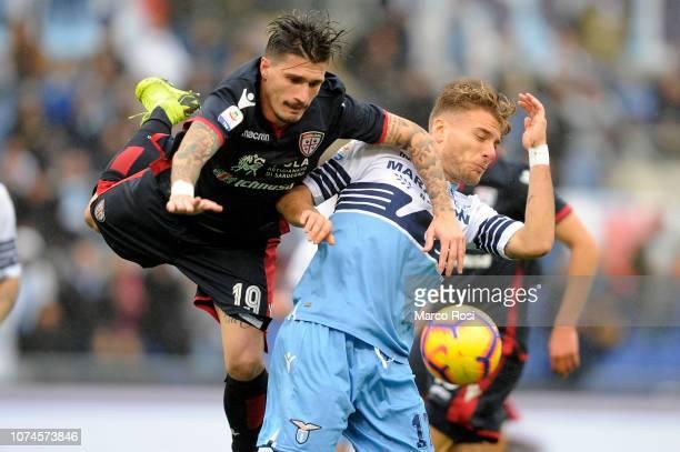Ciro Immobile of SS Lazio compete for the ball with Fabio Pisacane of Cagliari during the Serie A match between SS Lazio and Cagliari at Stadio...