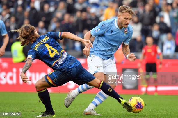 Ciro Immobile of SS Lazio compete for the ball with Jacopo Perticone of US Lecce during the Serie A match between SS Lazio and US Lecce at Stadio...