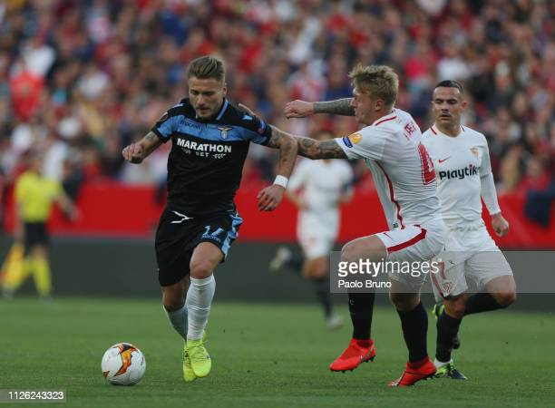 Ciro Immobile of SS Lazio competes for the ball with Simon Kjaer of Sevilla during the UEFA Europa League Round of 32 Second Leg match between...