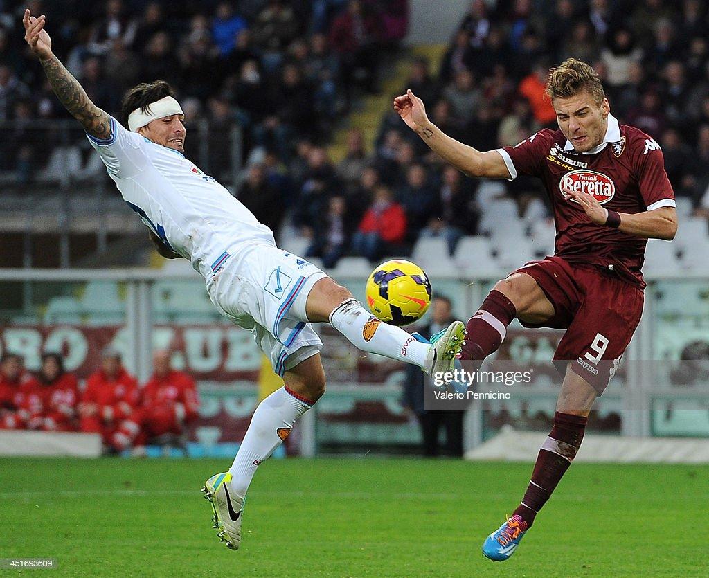 Ciro Immobile (C) of Torino FC is tackled by Pablo Alvarez (L) of Calcio Catania during the Serie A match between Torino FC and Calcio Catania at Stadio Olimpico di Torino on November 24, 2013 in Turin, Italy.