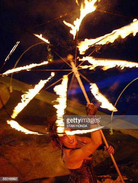 Cirque du Soleil performer holds a wheel of fire at the opening ceremonies 16 July 2005 for the 2005 XI FINA World Championships that will take place...